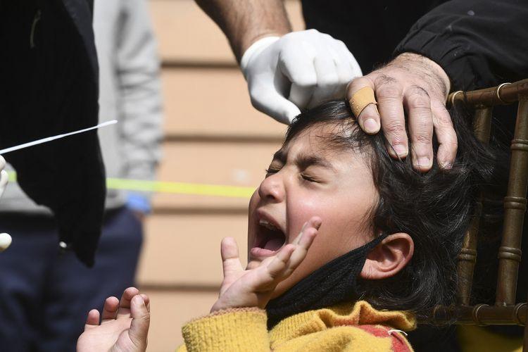 Petugas medis mengambil sampel lendir dari tes swab Covid-19 seorang gadis cilik, di Srinagar, India, pada 21 April 2021.