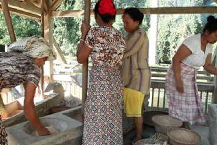 Ibu-ibu di Kampung Naga, Tasikmalaya, Jawa Barat, menumbuk padi hasil panen.