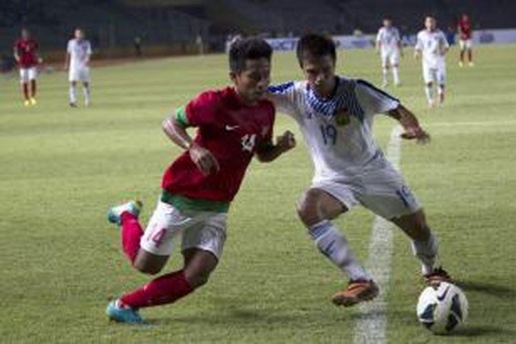 Pemain Indonesia, Andik Vermansah berusaha melewati hadangan pemain Laos pada laga MNC Cup di Stadion Utama Gelora Bung Karno, Kamis (21/11/2013). Pada laga ini Indonesia berhasil menang dengan skor 3-0.
