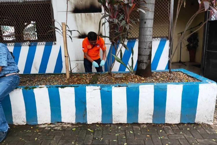 Polisi saat melakukan olah tempat kejadian perkara (TKP) di pos polisi lalu lintas di Makassar usai dilempari bom molotov, Minggu (13/12/2020).