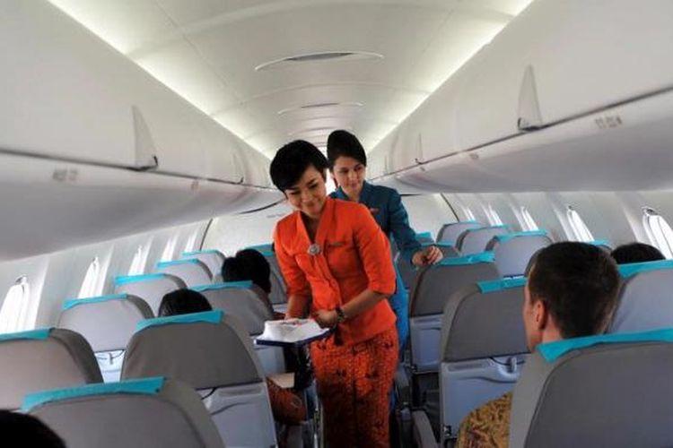 Pramugari Garuda Indonesia melayani penumpang.