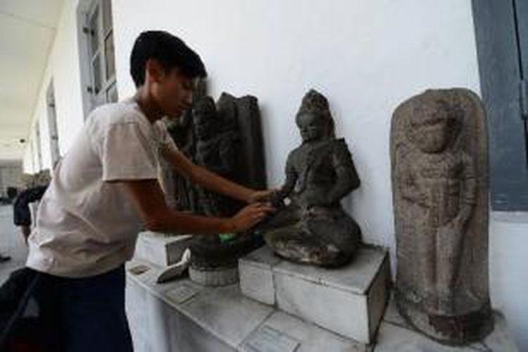Pekerja membersihkan kotoran pada arca-arca koleksi Museum Nasional di Jakarta, Minggu (1/9/2013). Pembersihan ini untuk menjaga kondisi arca tetap seperti wujud aslinya dan meminimalkan kerusakan akibat kotoran atau tangan jahil pengunjung.