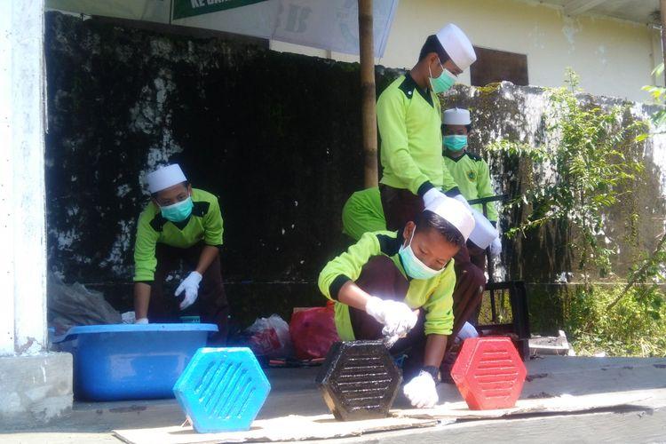 Santi mewarnai dan mengeringkan paving berbahan sampah plastik. Di pesantren ini, sampah disulap menjadi benda bernilai ekonomi.