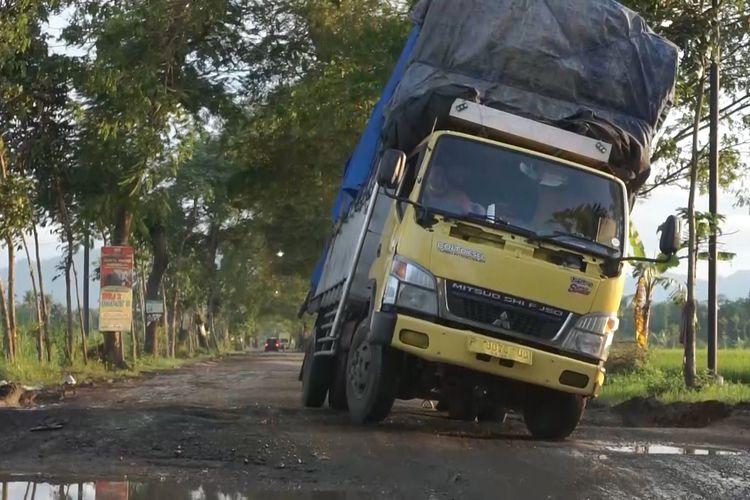 Truk yang hampir terguling karena berusaha melintas diantara jalur yang rusak, yang berada di kecamatan Karangan Trenggalek.