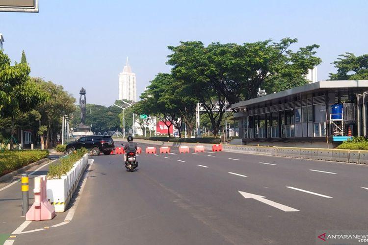 Pengendara sepeda motor melintas di Jalan Sudirman dan dialihkan menuju Jalan Senopati karena arah Bundaran Senayan, Jakarta ditutup sementara pada hari pertama PPKM Darurat, Sabtu (3/7/2021).