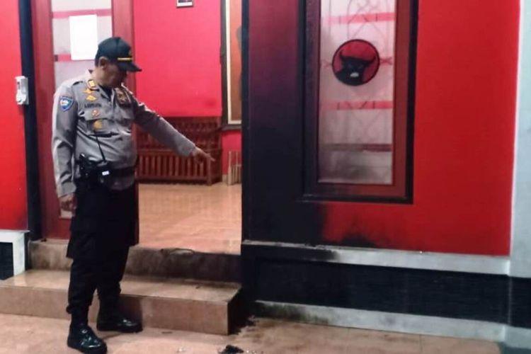 Seorang anggota Polri memerlihatkan kondisi pintu depan kantor sekretariat PDIP Cianjur yang terbakar setelah dilempari bom molotov orang tak dikenal, Jumat (7/8/2020) dini hari.