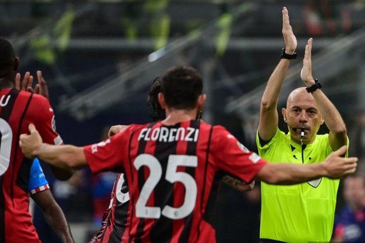 Wasit Cuneyt Cakir memberikan gestur pertanda handsball di kotak penalti pada laga Grup B Liga CHampions AC Milan vs Atletico Madrid pada Rabu (29/9/2021) dini hari WIB di Stadion San Siro, Milan.