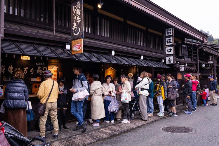 Orang-orang mengantre dengan tertib untuk membeli Hida beef Sushi di Takayama old town, Jepang.
