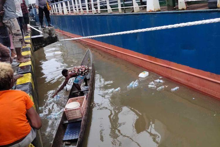 Polisi menyewa perahu masyarakat ikut membantu membersihkan botol plastik yang terbuang di laut pinggir dermaga Poumako. Ini dilakukan setelah pemusnahan miras pada Sabtu (3/4/2021).