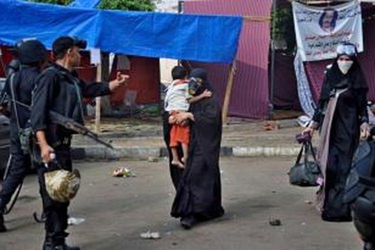 Pasukan keamanan Mesir mengawal seorang wanita dengan seorang anak saat pasukan keamanan membersihkan kamp yang didirikan para pendukung Presiden Mesir terguling Muhammad Mursi di dekat Universitas Kairo, Giza, Mesir, 14 Agustus 2013.