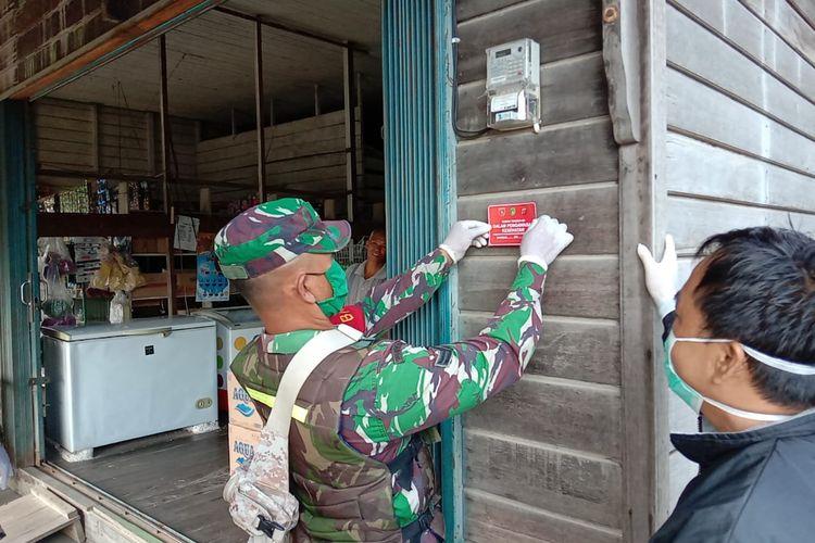 Petugas kesehatan dibantu aparat sedang menempel stiker rumah orang dalam pemantauan (ODP) di Kabupaten Kutai Kertanegara, Kalimantan Timur, Sabtu (28/3/2020).