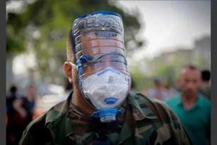 Seorang pria mengenakan masker gas buatan sebelum polisi anti huru-hara menggunakan gas air mata dan jet air untuk membubarkan demonstrasi anti-pemerintah di sebuah taman di Istanbul, Turki, 20 Mei 2013.