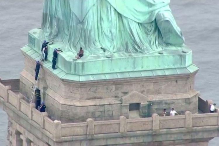 Polisi sedang berbicara dengan seorang perempuan yang naik ke Patung Liberty di New York pada Rabu (4/7/2018). (AFP/PIX11 News)