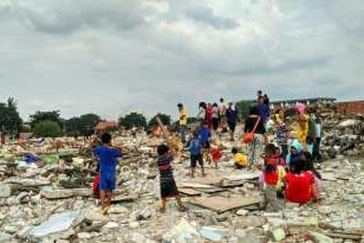 Anak-anak Pasar Ikan, Penjaringan, Jakarta Utara, bermain perang-perangan di atas puing-puing sisa penggusuran. Seorang anak tampak mengangkat kayu sebagai pedang yang dia gunakan untuk menyerang lawannya, Jumat (15/4/2016).
