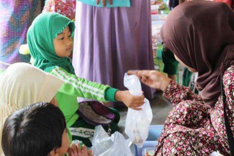 Seorang pengunjung sedang membeli jajanan kepada para pedagang cilik yang merupakan siswa PAUD TK IT Az Zahra, Takengon, Aceh Tengah, Aceh, Sabtu (5/3/2016).