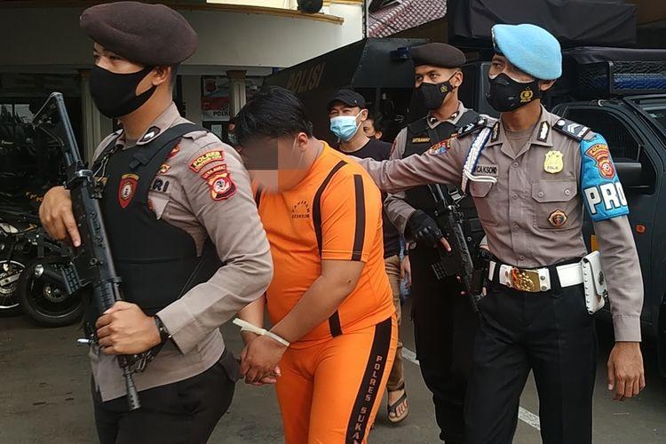Tersangka HFM mengenakan pakaian tahanan warna orange digiring petugas bersenjata lengkap di Polres Sukabumi Kota, Jawa Barat, Selasa (4/5/2021).