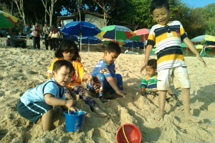 Anak bermain pasir di pantai sambil belajar.