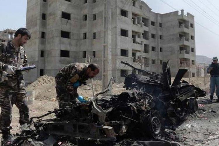 Tentara Afghanistan memeriksa lokasi serangan bom yang dilakukan oleh gerilyawan Taliban di Bandara Kabul, Afghanistan, 17 Juli 2014.