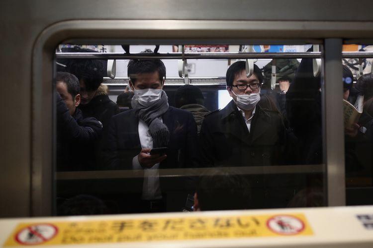 Penumpang kereta commuter di Tokyo, Jepang, mengenakan masker pelindung, menyusul penyebaran virus Corona dari Kota Wuhan China, 28 Januari 2020.
