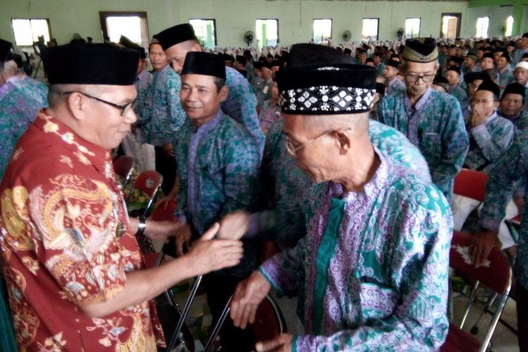 Bupati Demak,  M Natsir menyalami para calon jamaah haji Demak,  seusai acara pembekalan dan pelepasan pemberangkatan calon jamaah haji di Gedung IPHI Demak,  Rabu (25/7/2018)