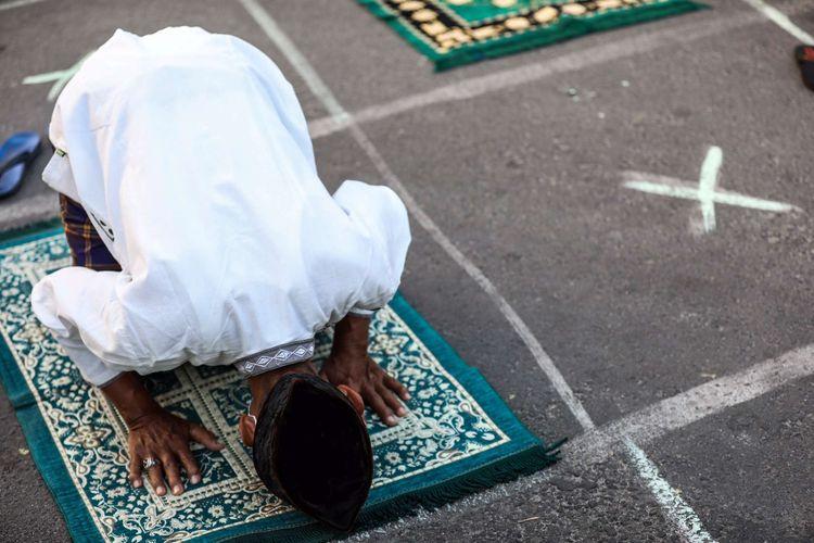 Umat muslim melaksanakan shalat Idul Adha di Jalan Pramuka Raya, Cempaka Putih, Jakarta Timur, Jumat (31/7/2020). Umat muslim menggelar shalat Idul Adha secara berjamaah dengan menerapkan protokol kesehatan seperti jaga jarak serta wajib mengenakan masker guna mencegah penyebaran COVID-19.