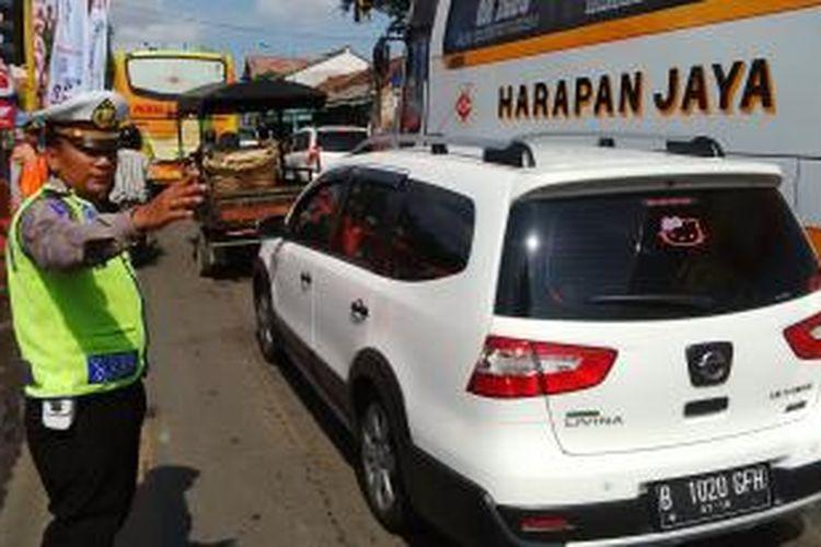 Kasatlantas Polres Brebes Akp Arfan Zulkan Sipayung melakukan pengaturan arus lalu lintas yang mengalami antrian di Komplek Alun-Alun Brebes, Minggu (27/12/2015).