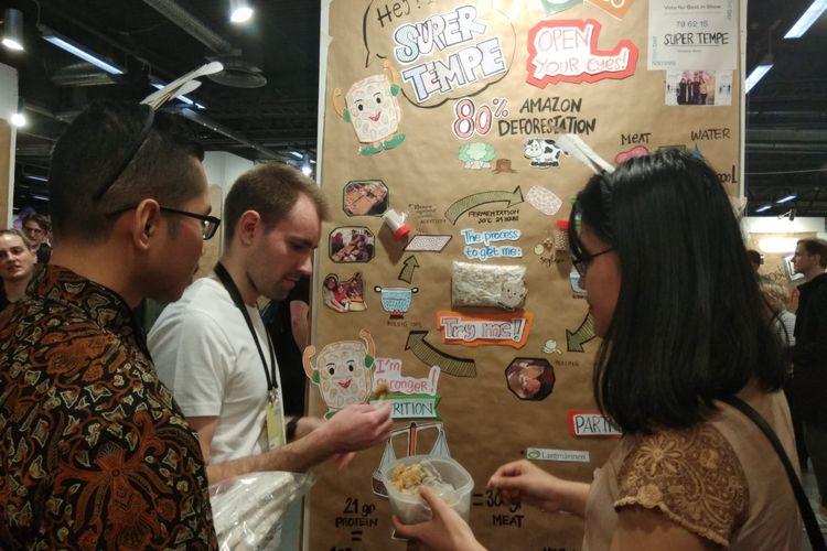 Seorang pengunjung Sweden Demo Day mencicipi tempe goreng tepung yang disuguhkan tim Super Tempe. Mahasiswa asal Indonesia memperkenalkan tempe sebagai makanan alternatif sekaligus ide bisnis di ajang temu ribuan startup dan investor Swedia di Stockholm, Kamis (4/4/2019)