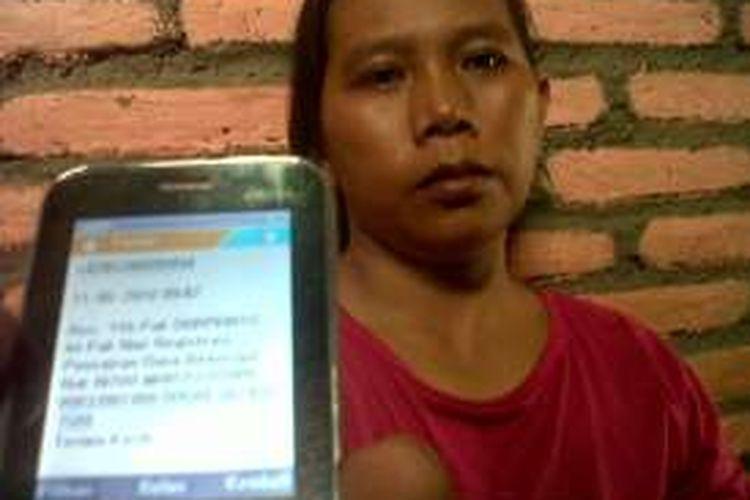 Sri Wahyui ( 30 ), warga Gebang RT 3 RW 1, Kecamatan Bonang, Demak ,  korban penipuan beasiswa prestasi menunjukan  nomor registrasi yang di kirim pelaku ke ponselnya, Rabu (11/5/2016)