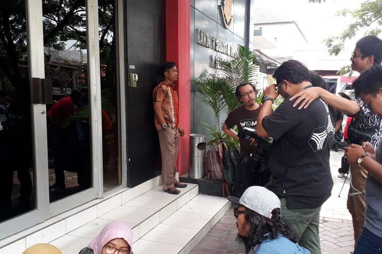 Puluhan wartawan bergerombol di depan salah satu pintu masuk gedung Ditreskrimsus Polda Jawa Timur, Jumat (15/3/2019) siang.