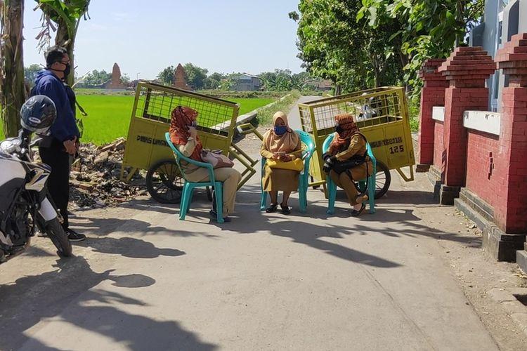 Sejumlah gerobak tempat sampah menutupi jalan keluar masuk desa Tusmi Kulon , yang berbatasan dengan Desa Wotgali Kecamatan Plered Kabupaten Cirebon, (Senin 27/7/2020). Sejumlah perangkat desa duduk dan teus memberikan edukasi dan sosialisasi kepada warga.