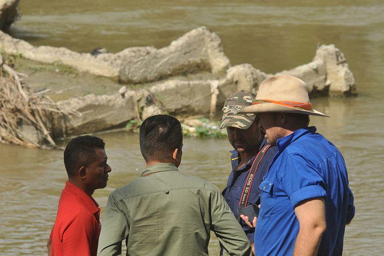 Warga negara Australia, Matthew Nicolas Wright (kedua kanan) dan Chris Wilson (kanan) berbincang dengan petugas saat memantau lokasi kemunculan seekor buaya liar yang terjerat ban sepeda motor di Sungai Palu di Palu, Sulawesi Tengah, Selasa (11/2/2020). Dua ahli penanganan satwa liar asal Australia tersebut hadir di Kota Palu untuk membantu operasi penyelamatan buaya terjerat ban yang dilaksanakan oleh Satgas dari Balai Konservasi Sumber Daya Alam (BKSDA) Sulawesi Tengah yang hingga kini belum membuahkan hasil.