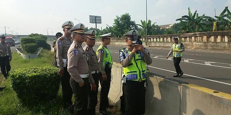 Petugas kepolisian dari Direktorat Lalu Lintas Polda Metro Jaya melakukan uji coba pembatasan kecepatan dengan menggunakan Speed Gun di tol yang mengarah ke bandara pada KM 25-900, Jakarta, Sabtu (12/3/2016).