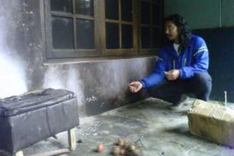 Frietqi Suryawan alias Demang, wartawan Radar Jogja memperlihatkan kondisi rumahnya setelah dilempari bom molotov oleh orang tidak dikenal, Senin (24/2/2014).