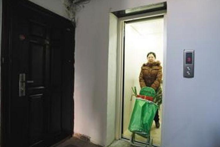 Penghuni gedung menggunakan fasilitas lift yang baru-baru ini dipasang di apartemen tempat tinggalnya di China.