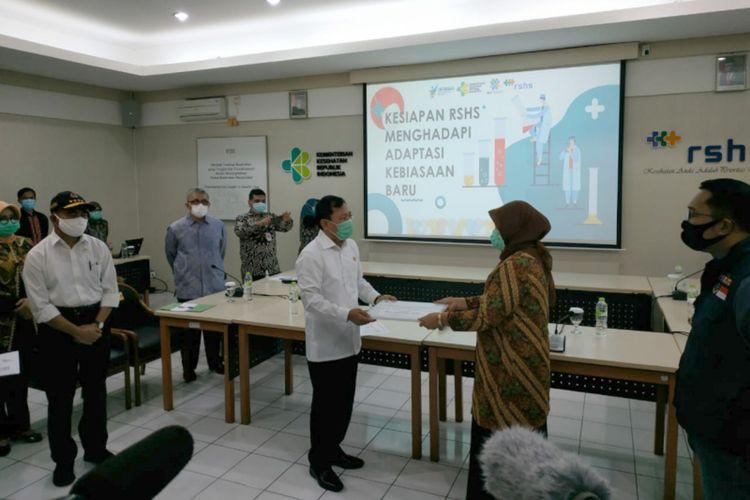 Menteri Kesehatan Terawan Agus Putranto saat memberikan santunan bagi perwakilan keluarga tenaga medis saat berkunjung ke Rumah Sakit Hasan Sadikin (RSHS) Bandung, Sabtu (20/6/2020).