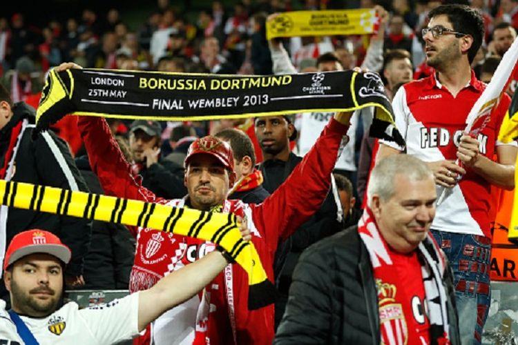Suporter AS Monaco membentangkan syal Borussia Dortmund untuk menunjukkan empati atas terjadinya ledakan di dekat bus tuan rumah, sekitar 10 kilometer dari Stadion Signal Iduna Park, Selasa (11/4/2017).