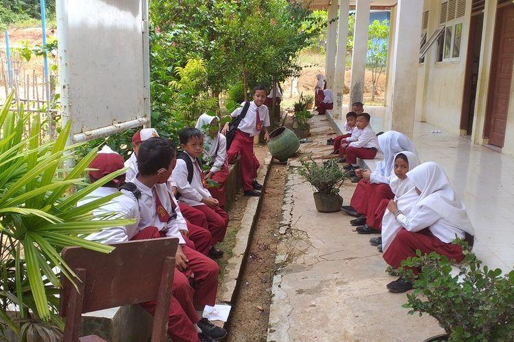 Murid SDN 028 dari anak-anak Suku Talang Mamak sedang duduk-duduk di depan sekolahnya sebelum pulang ke rumah di Desa Talang Sungai Limau, Kecamatan Rakit Kulim, Kabupaten Inhu, Riau, Senin (2/11/2020).