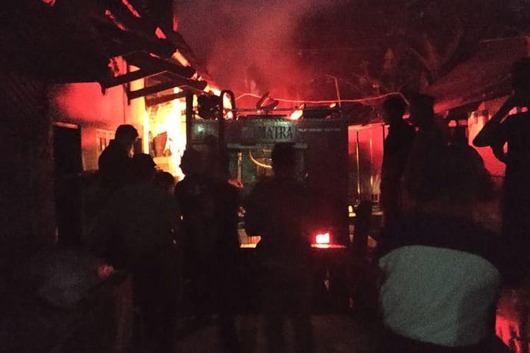 Petugas berupaya memadamkan kebakaran di pabrik tahu.