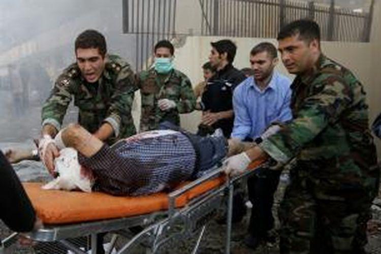 Tentara Lebanon membawa seorang korban luka akibat dua ledakan keras yang terjadi di luar Kedutaan Besar Iran di Beirut, Selasa (19/11/2013). Ledakan itu menewaskan sedikitnya tujuh orang.