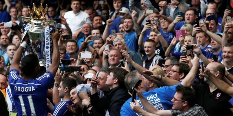 Penyerang Chelsea, Didier Drogba, saat mengangkat trofi Premier League di depan pendukungnya seusai mengalahkan Sunderland 3-1 pada laga terakhir Premier League 2014-15 di Stamford Bridge, Minggu (24/5/2015).