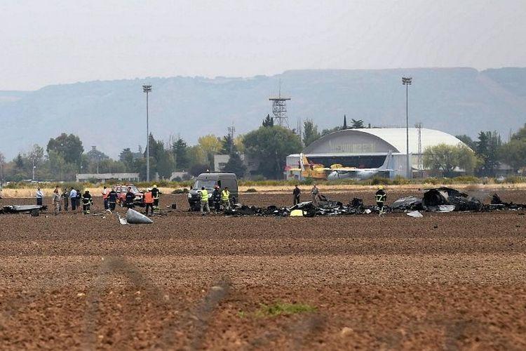 Petugas dari badan penyelamat Spanyol berjalan di tengah serpihan pesawat F-18 Hornet yang jatuh di dekat Pangkalan Torrejon de Ardoz (17/10/2017)