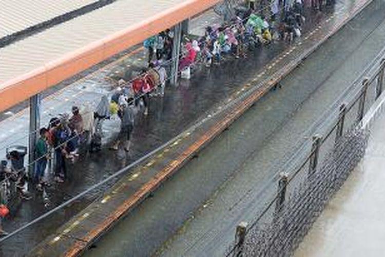 Warga menunggu kedatangan kereta komuter dari arah Serpong di Stasiun Tanah Abang, Jakarta Pusat, Senin (9/2/2015). Hujan yang turun sepanjang hari di Jabodetabek membuat sejumlah wilayah tergenang, termasuk di Stasiun Tanah Abang. Akibatnya, perjalanan kereta komuter terganggu sejak Senin pagi hingga menjelang malam.