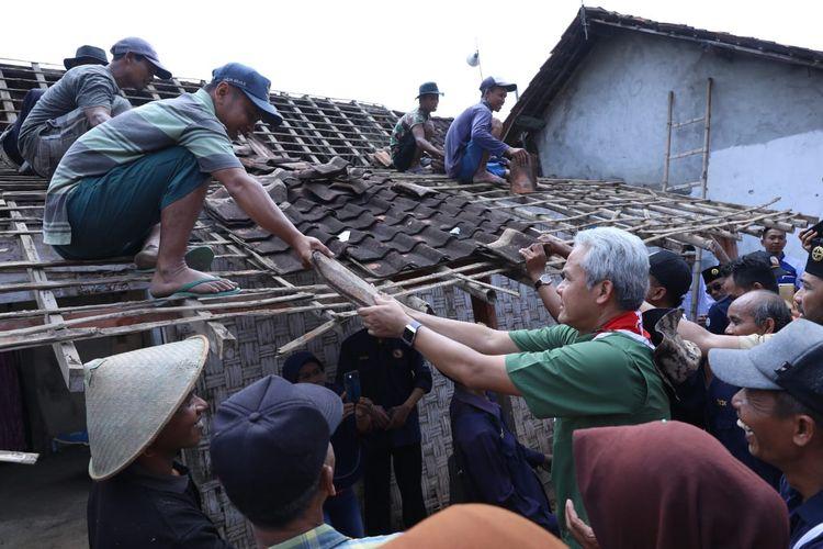 Gubernur Jawa Tengah (Jateng) Ganjar Pranowo bersama masyarakat dan anggota Pramuka Peduli ikut membongkar rumah Mbah Dami (82) yang mendapat bantuan renovasi dari Pemerintah Provinsi Jateng, di Blora, Selasa (27/8/2019).