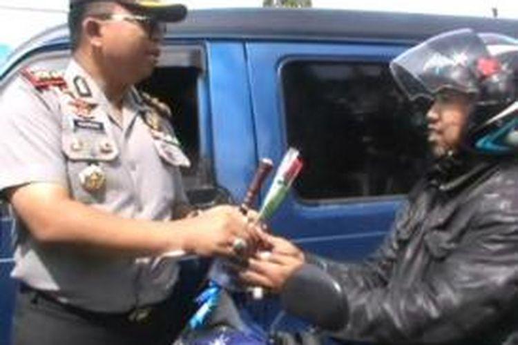 Pelanggar lalu lintas di Polewali Mandar, Sulawesi Barat, justru mendapat hadiah helm standar dan bunga dari petugas kepolisian saat kedapatan melanggar lalu lintas di jalan raya, Jumat (17/4/2015).