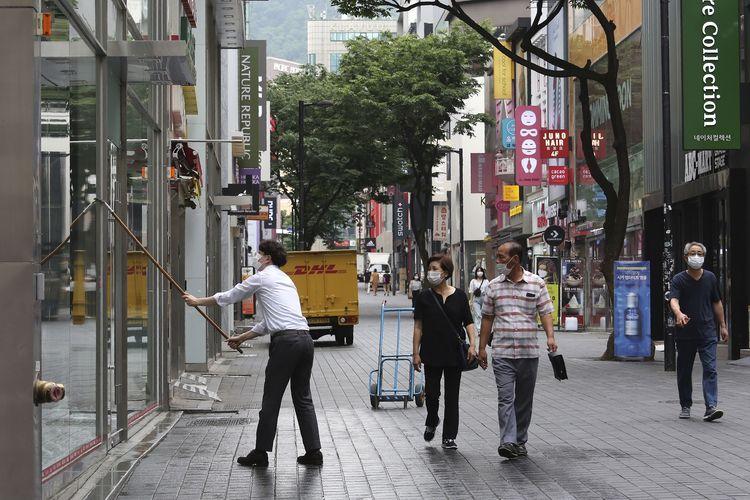 Seorang pegawai terlihat memakai masker untuk melindungi diri dari virus corona, saat membersihkan jendela toko sepatu di pusat perbelanjaan Seoul, ibu kota Korea Selatan, pada 12 Juni 2020.