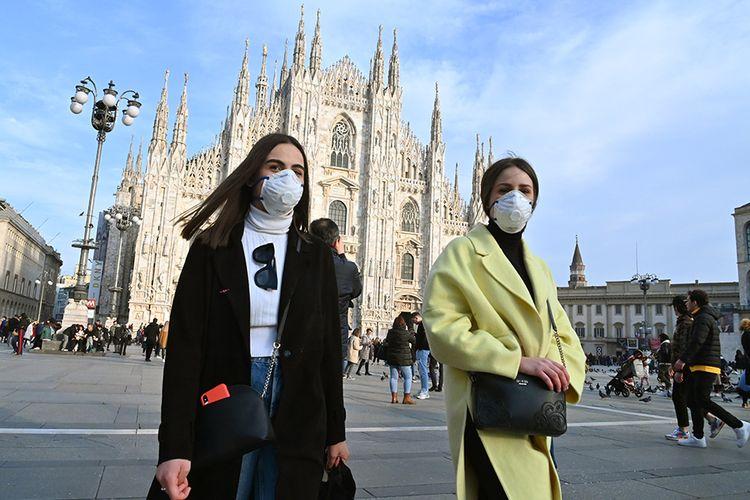 Warga mengenakan masker wajah guna mengantisipasi penyebaran virus corona saat berjalan melintasi Piazza del Duomo di Milan, Italia, Minggu (23/2/2020). Penyebaran virus corona hingga hari ini, Senin (24/2/2020), semakin menunjukkan peningkatan di sejumlah negara, seperti Italia, Iran, dan Korea Selatan.