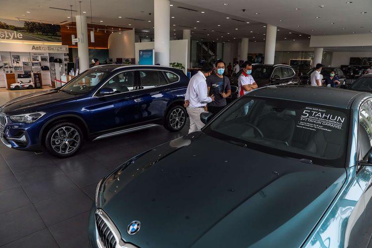 Pengunjung melihat kendaraan BMW terbaru saat BMW On Tour di dealer BMW Astra Serpong, Tangerang, Sabtu (17/10/2020). BMW Indonesia menggelar program penjualan pada masa PSBB transisi pandemi Covid-19 di 8 jaringan diler resmi BMW Group Indonesia dengan menerapkan protokol kesehatan dan sanitasi.