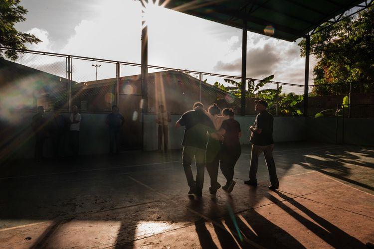 Guru membopong muid yang pingsan karena kelaparan di Venezuela.
