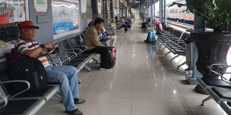 Penumpang menunggu kedatangan kereta api di peron Stasiun Pasar Senen, Jakarta setelah melakukan proses boarding yaitu pengecekan tiket dan identitas diri.