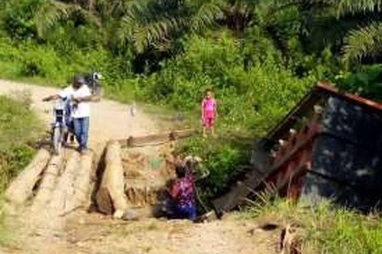 Warga melintas di jembatan kayu di Desa Gunci, Kecamatan Sawang, Aceh Utara, Jumat (29/4/2016) yang  ambruk mengakibatkan  truk jatuh ke sungai. .